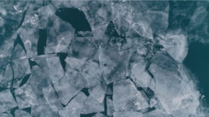 large pieces of lake ice float in a dark green Lake Michigan, layers of ice overlaid on top of one another
