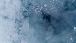 several layers of lake ice footage is layered over each other to create an otherworldy blue landscape with varying transparencies using a drone video camera