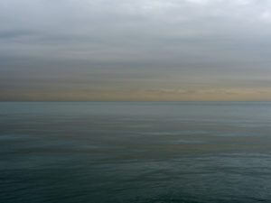 the sun is rising out of frame and lighting a deep green lake michigan while gray clouds are lit with a warm light that turns to yellows at the horizon separating the lake from the sky