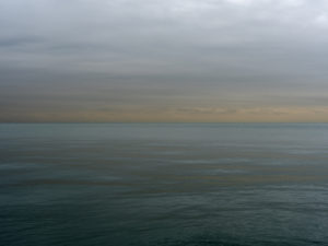 an early morning on lake michigan with the sun barely rising out of frame, green placid lake waters with heavy cloud cover in blues and siennas