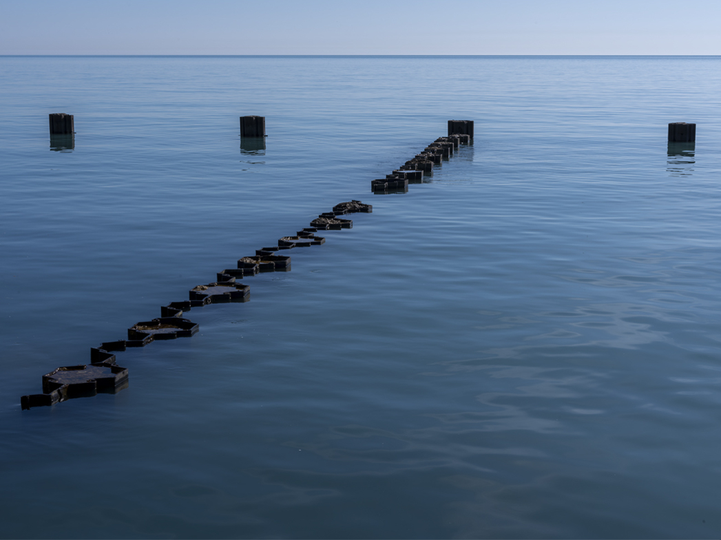 submerged breakwaters jut out into Lake Michigan, nearly obscured by the rich blue lake waters