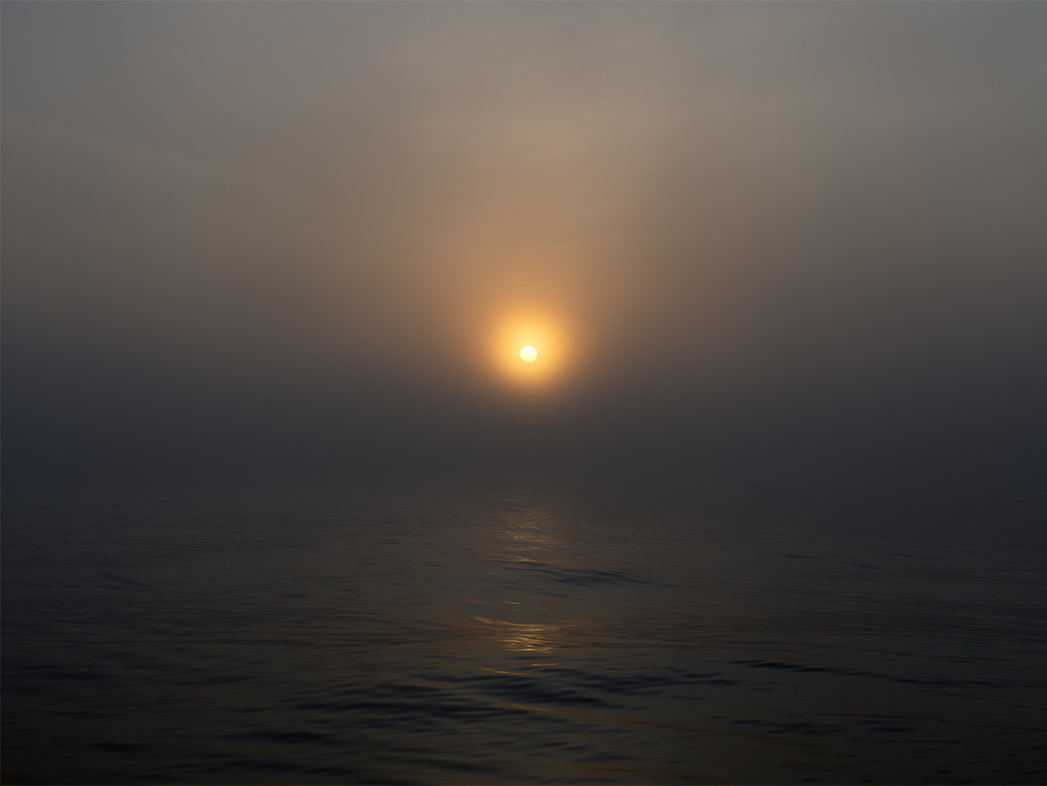 the sun sits just above the lake water, in a dramatic dark ombre sky of browns and blues and blacks, the sun is seen through a heavy fog it seems, with delicately lit water and waves beneath