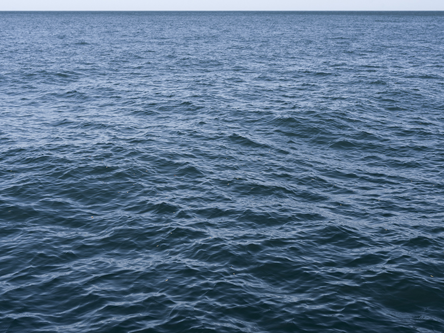 deep blue lake waters nearly fill the frame, with just a slight bit of light blue sky appearing on the horizon near the top, taken from the shore of Lake Michigan