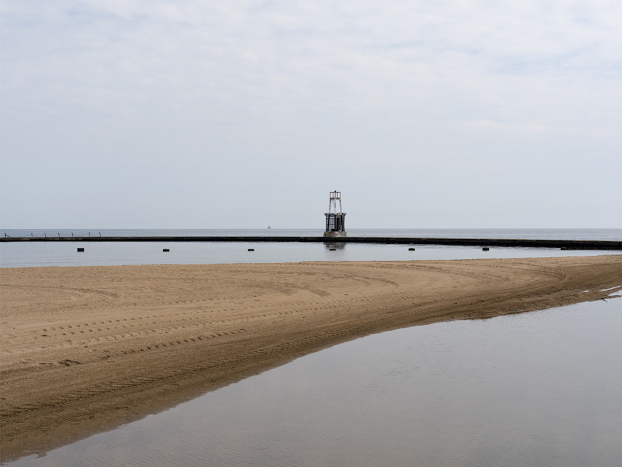 a light tower sits out on a scorpion tail break wall that protects the man made beaches of Lake Michigan from the waters off shore, from The Shore series by Lincoln Schatz