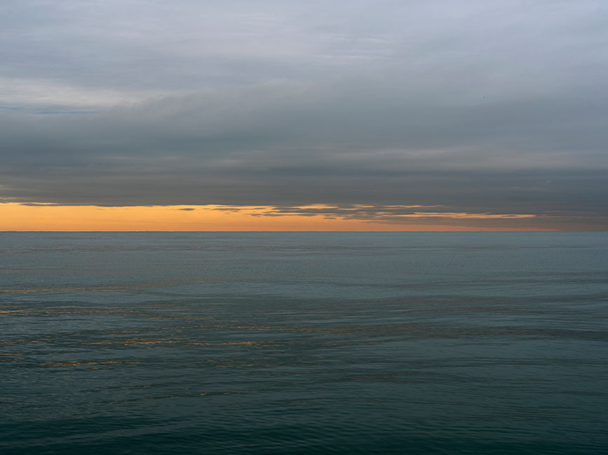 sun is rising and a brilliant golden horizon line with pastel gray clouds in the sky above and a rich green lake michigan