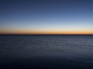 a beautiful sun rise on the lake features a deep blue to orange ombre in the sky over navy blue-blakc lake waters