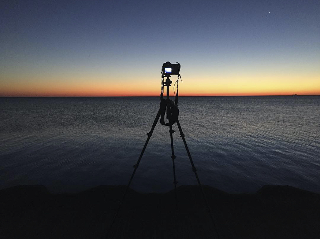 a behind the scenes sunrise photo of a camera on a tripod with a beautiful ombre blue to orange sunrise over a deep blue lake