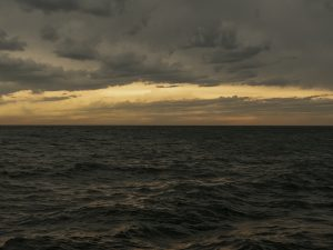 A dramatic lake picture of large waves beginning to form and move towards shore as storms build out over the water.