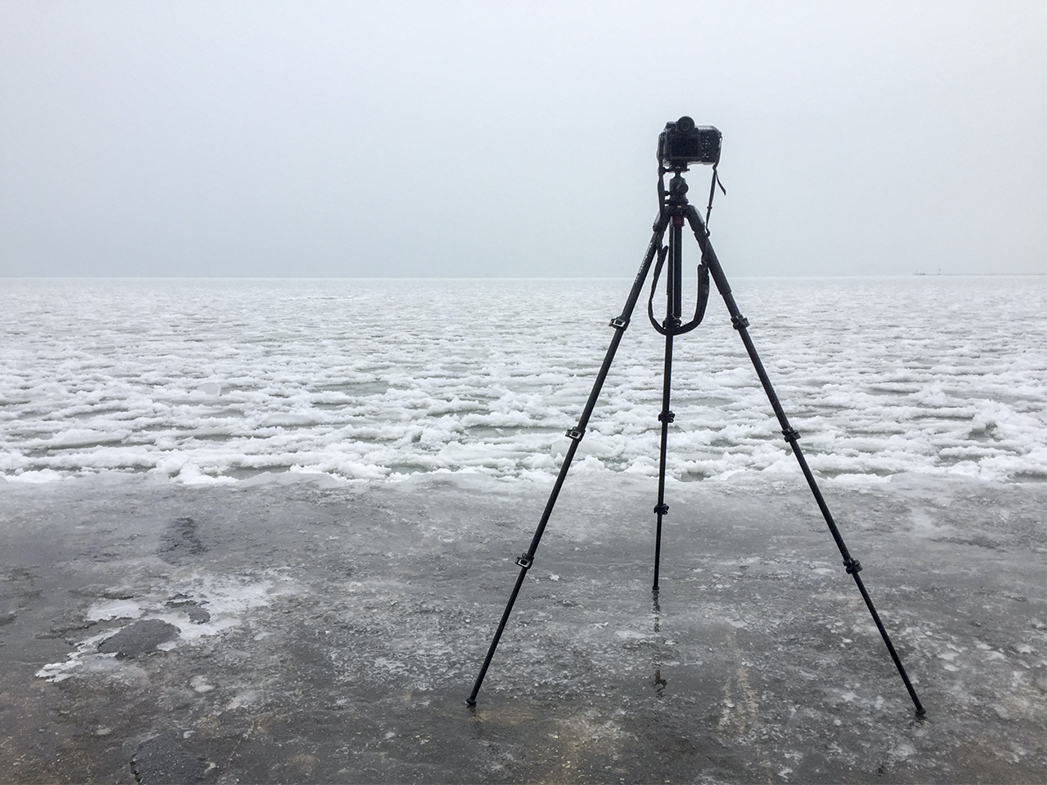 a camera sits on a tripod that is delicately balanced on an ice covered concete wall, Lake Michigan stretches in front, entirely coated in ice and snow, heavy fog sits over everything
