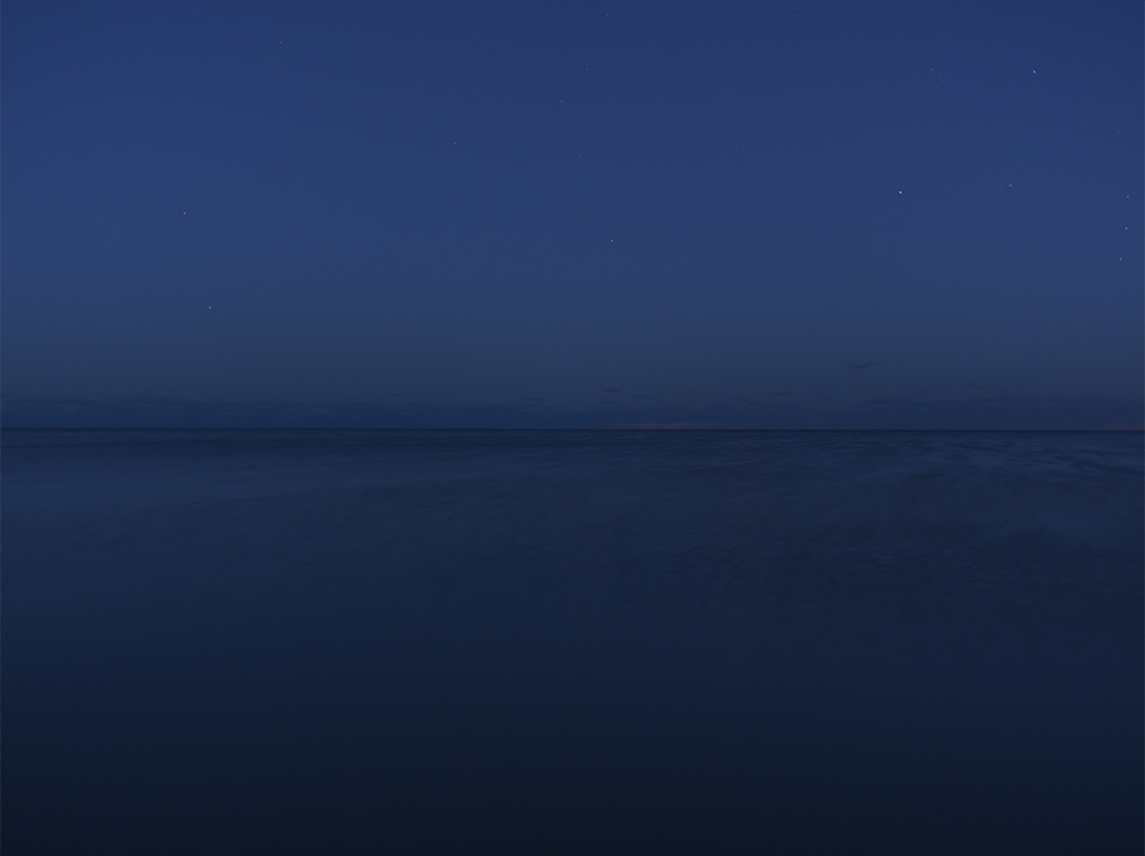 a midnight blue sky and water on Lake Michigan early before the sun rises on the lake