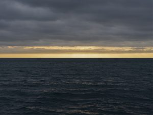 a dark morning and waves on Lake Michigan appear in black waters, where a golden horizon appears beneath dark gray clouds
