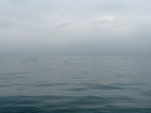 a calm lake photo where the sky is a light gentle gray with just touches of clouds showing their edges, over a smooth, gray green and soft Lake Michigan undulating