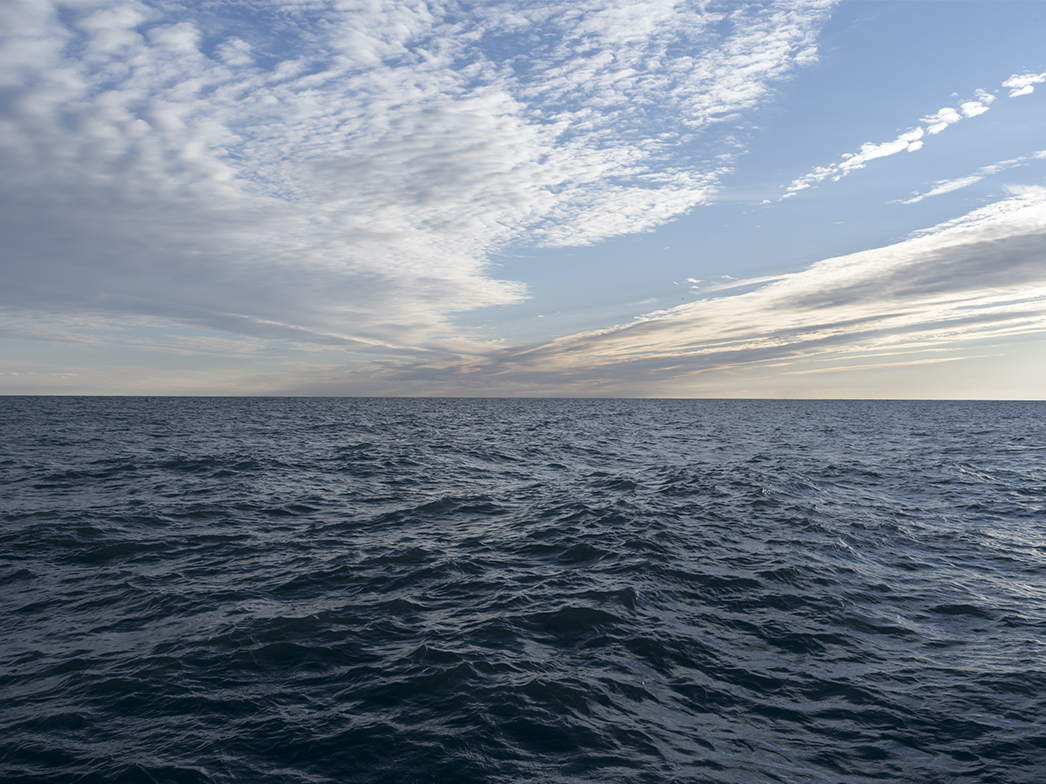 choppy lake waters are forming under clouds fanning out in a blue sky