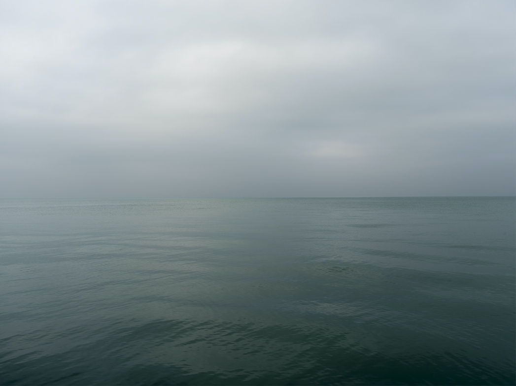 a lake fog photo where the sky and lake waters, both tinged green on this sunless day, merge together through the fog that hangs in the air