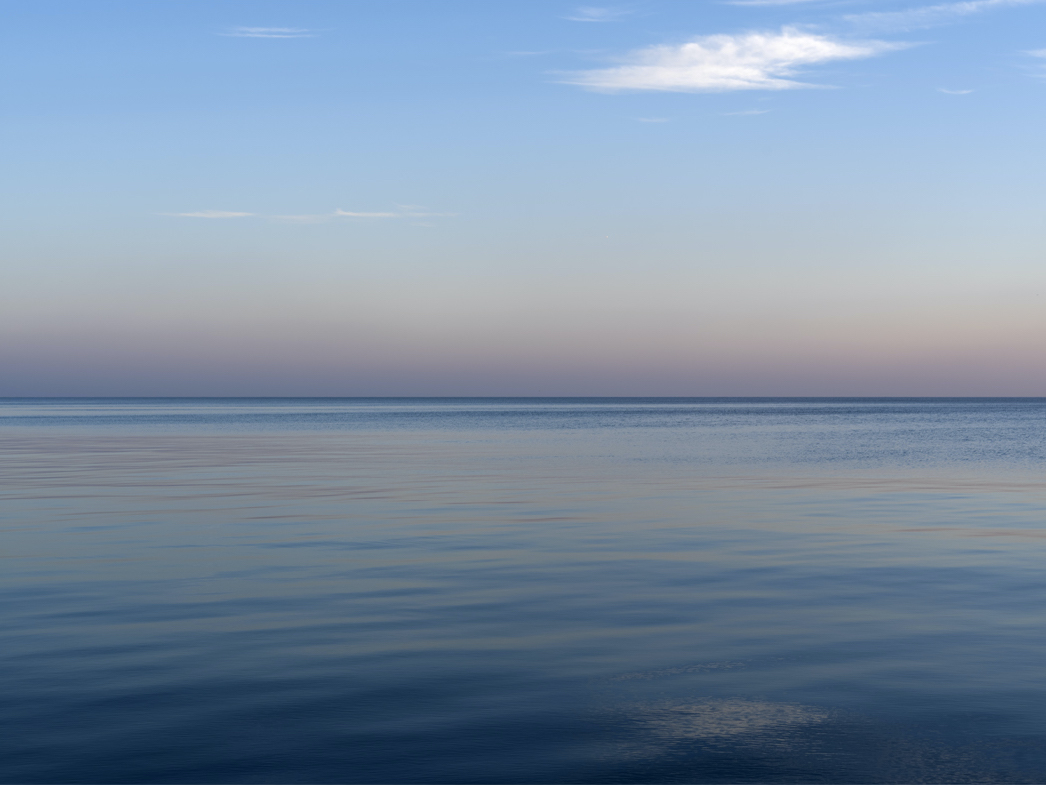 Lake and Sun Rise Early in December creates a still and smooth world of softly transitioning warm and cool blue tones on Lake Michigan