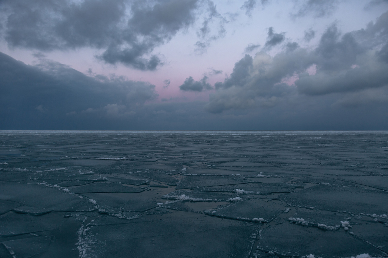 an Purple Sunrise Over a Frozen Lake Michigan, purple and blue tones fill the sky behind light blue gray cloud cover over a frozen dark blue lake