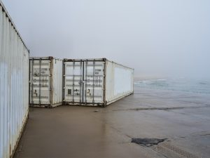dirty white shipping containers on the beach next to Lake Michigan in Chicago on a foggy and almost opaque day