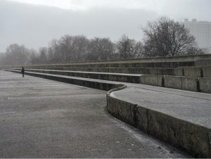 snow falls on the concrete steps and wall that rise out of the lake to keep the lake water at bay, the steps move inwards as they extend out in perspective, the clouds are heavy, light diffuse and snow falling on the entirely gray day