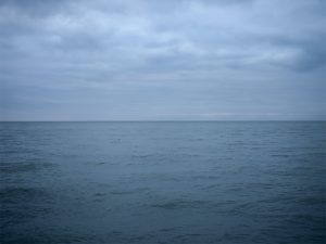 a somber lake photo early in the morning where the landscape and sky are infused with the same rich blue color, the light of day still low and sedate on Lake Michigan