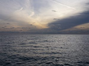 Unusual Clouds on the Lake layer together to create gauzy and distinct clouds in oranges, blues and purples over a rippling Lake Michigan