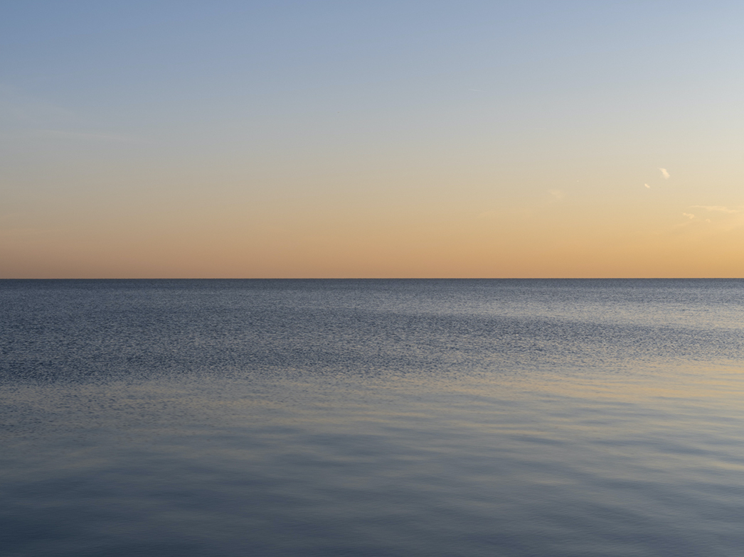 a winter sunrise where the sun is out of frame, the sky goes from orange to blue, in a steady shifting ombre, flat and cloudless it is reflected somewhat in the lake waters that ripple out further from shore in the winds of winter
