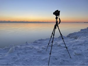 a cold frozen landscape on the edge of Lake Michigan, the colors are ethereal and light blues, peaches, soft light, delicate, a camera and tripod, large and black, sit on ice