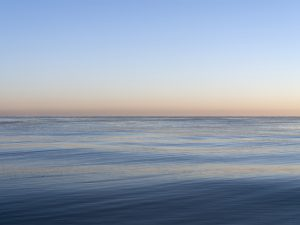 a crystal clear lake michigan with a perfectly blue sky over head that shifts to warm peach tones by the time it reaches the horizon, the lake is nearly still, gentle rolling waves