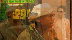 a video still of Will, Joseph and Lamont being interviewed in front of their store, with mutiple camera angles and layers appearing over one another, from the Cure Violence project