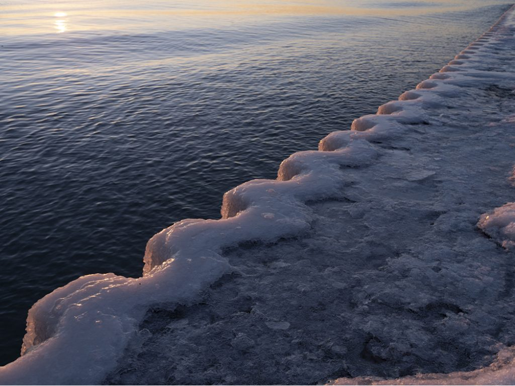 an icy lake wall along Lake Michigan, when the water has frozen in layers slowly over time as waves crash against the concrete and steel barricade