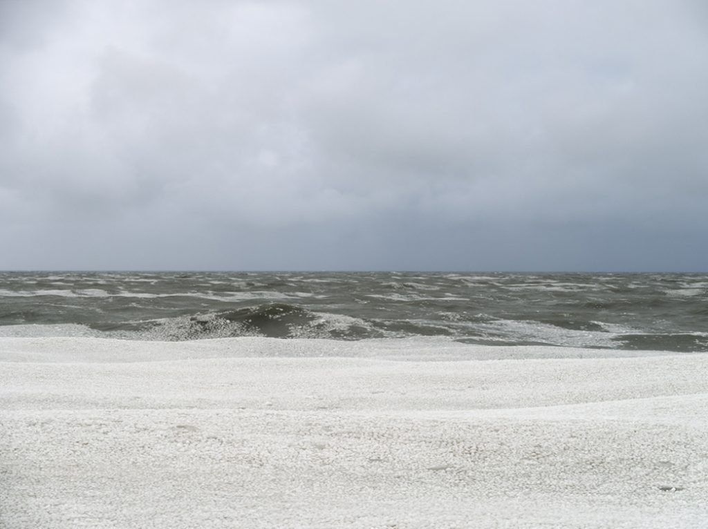 the lake ice, once large blocks, has become a floating expanse of small pieces on top of large foaming green waves on Lake Michigan, under a cloudy gray sky