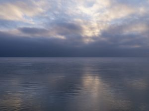 the lake forms a mirror under a beautiful sky where the early morning sun is pushing behind clouds, from the Lake Series, February 2021