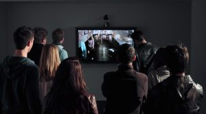 a single screen mounted on the wall sits in front of viewers in a darkened room, the screen displays Cluster, a generative video art portrait by Lincoln Schatz