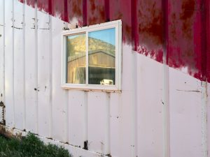 a shipping container fills the frame, painted white and red in a diagonal slash, a window has been installed that shows the hills of the Vernal Utah landscape photo by Lincoln Schatz