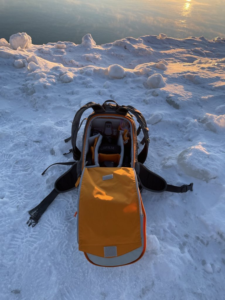 Camera Gear Bag of Lincoln Schatz sits on an ice covered shoreline of Lake Michigan early in the morning