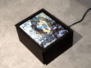 End of Boom sits on the floor of a studio displaying the artwork running inside of a metal frame