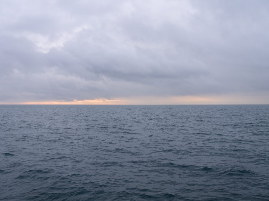 a peach lake horizon photo from the Lake Series, photographs of Lake Michigan by artist Lincoln Schatz, the lake waters are a gray green and the clouds have a purplish hue above the peach lake horizon