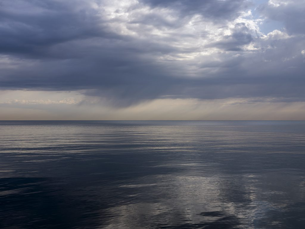 Storm Clouds Open over lake michigan early in the morning in this photo by Lincoln Schatz
