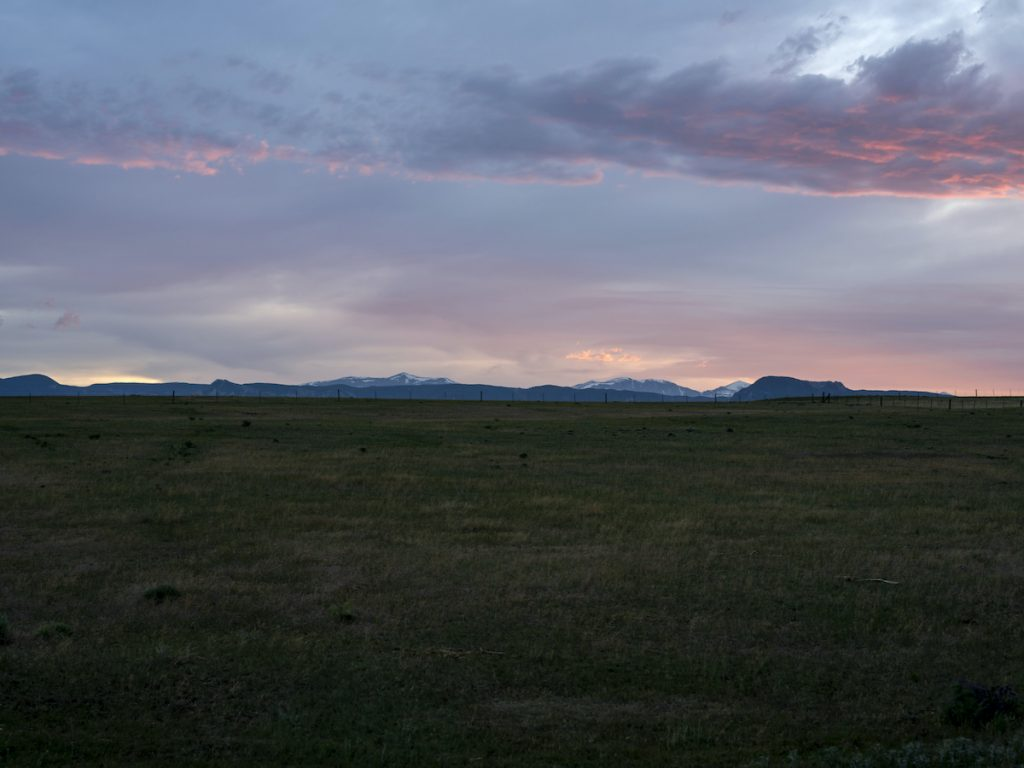Sunset Over Bighorn Mountains and the sky is cloudy with pastel hues and the grasslands beneath lay in shadow