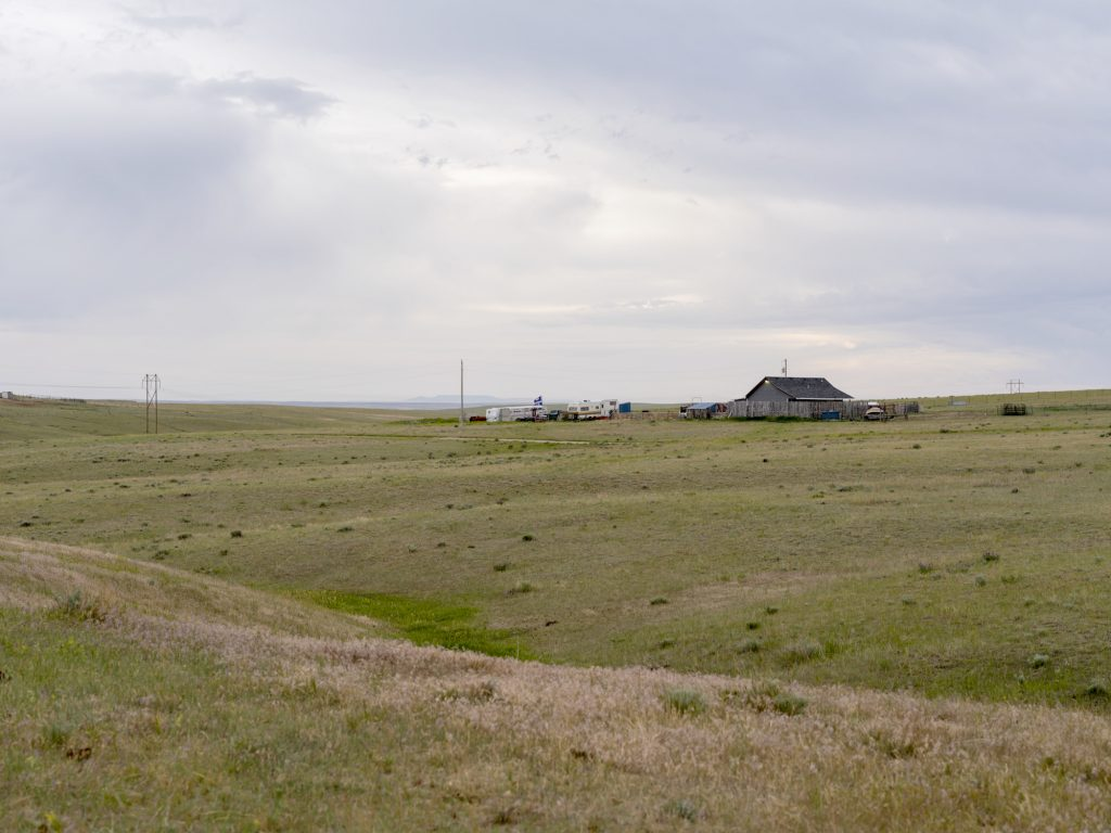 Wyoming Ranch Land is desolate under a gray and cloudy sky, the land stretching away from a small house and outbuildings surrounded by vehicles of various types