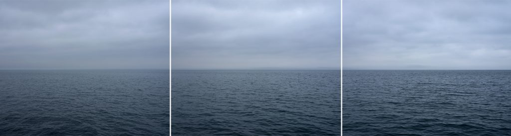a stormy lake panorama photo from Lincoln Schatz of Lake Michigan, covered in heavy clouds, the water dark green