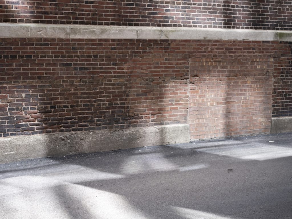 Sunlight in an Alley reflects and refracts off of the towers above it, creating varying light opacities in squares and rectangles on the wall of a brick building and on the ground in the alley