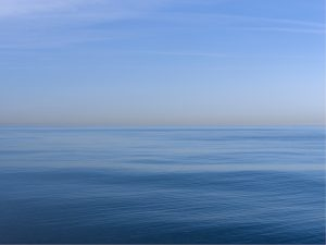 a May lake photo where the lake is serene and the waters gently rolling, the sky and water all in tones of blue