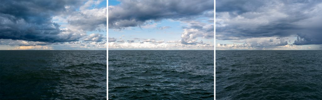 a large lake panorama photo with storm clouds forming in a blue sky over dark green blue lake waters