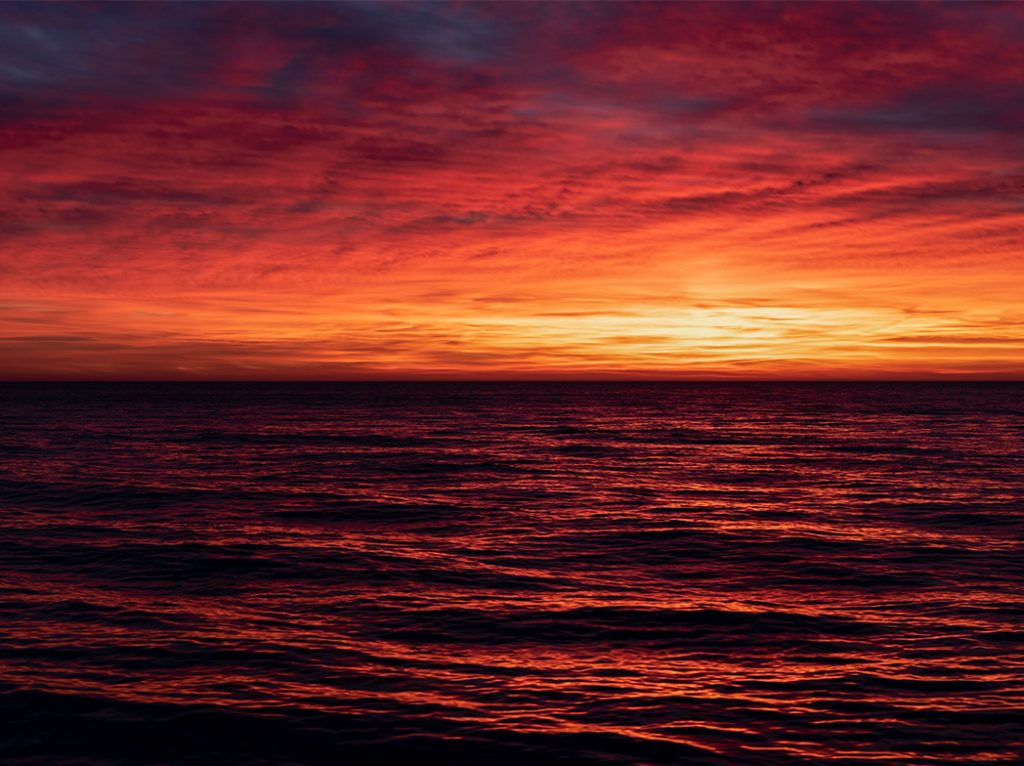 red skies in morning are causing Lake Michigan and the skies above to appear to be on fire, brilliant reds, yellows and oranges make this photo by Lincoln Schatz glow with warmth
