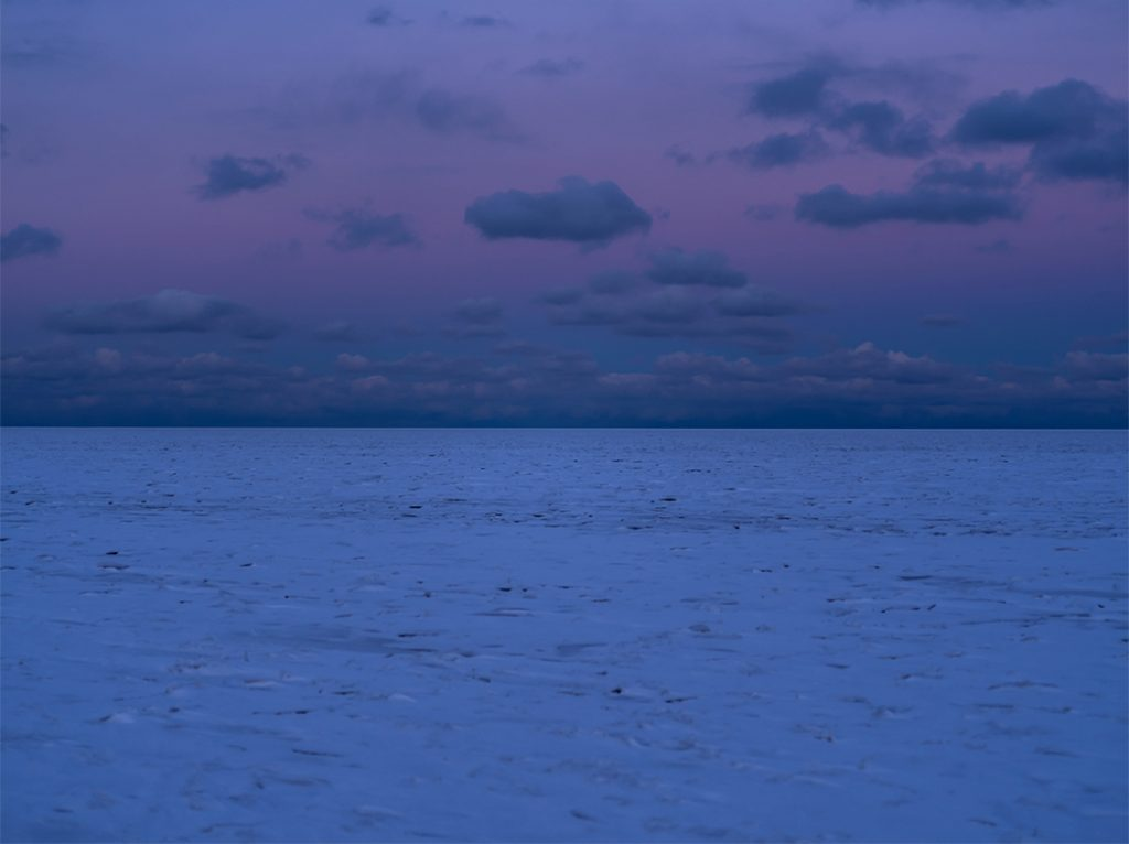 a purple dawn on Lake Michigan where the lake is solid frozen ice covered in snow, the sky a purple blue
