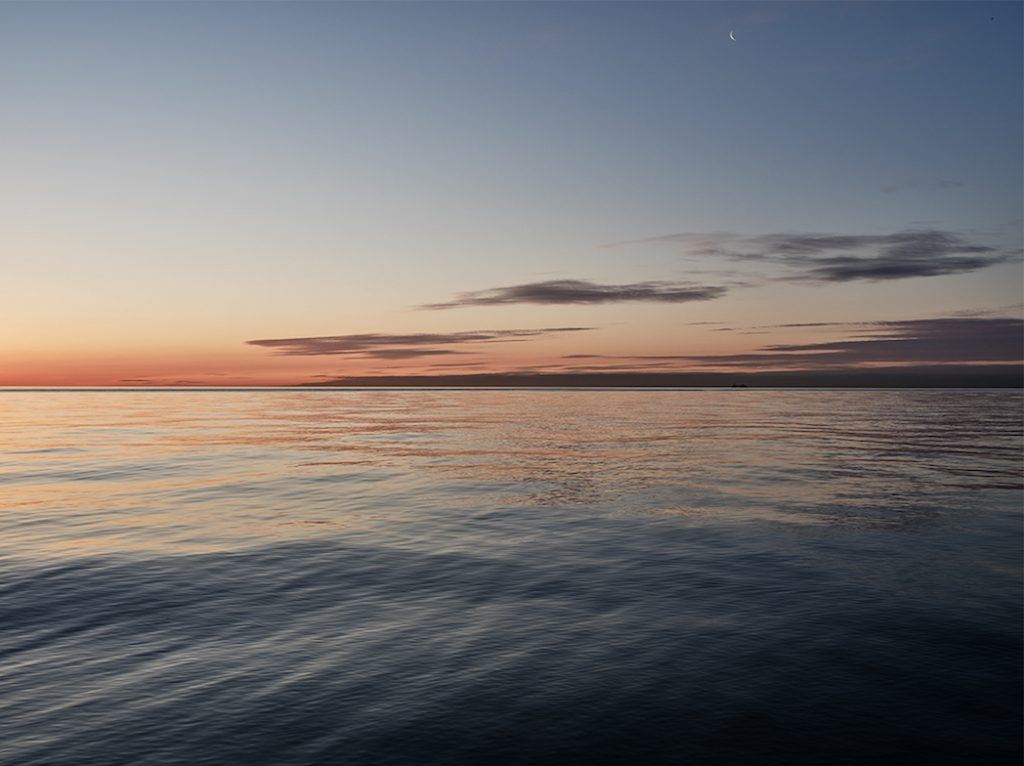 a sliver of moon appears in beautiful ombre skies over a still Lake Michigan