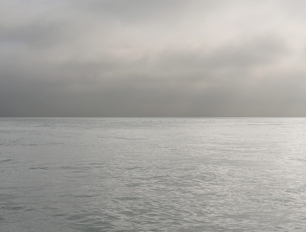 silvery lake waters match the gray and silver in the clouds in the sky above