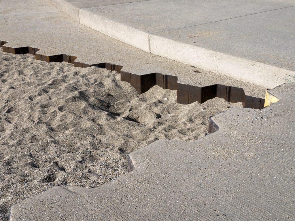 The lake wall, built here using steel and concrete, creates a seemingly indestructible barrier on the side of a man-made beach along the lakefront. The lake wall intersects with itself and concrete, dappled sand is contained in the corner