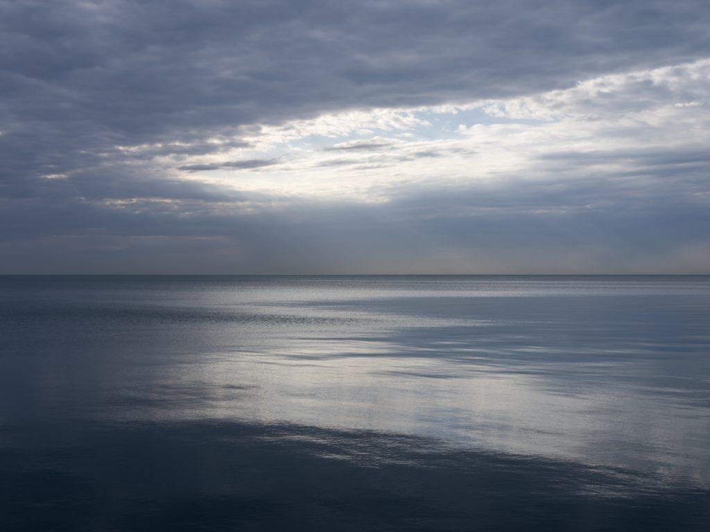 lake michigan along chicago has taken on mirror like qualities, reflecting the light pouring through an opening in the cloudy sky, while rains fall out over the horizon