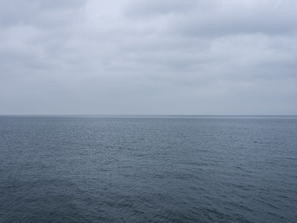 a gray sedate lake morning with heavy clouds in the sky